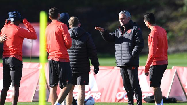 Manchester United's Portuguese manager Jose Mourinho (2R) talks with his players.