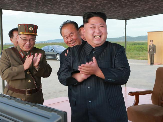 North Korean leader Kim Jong Un, right, celebrates what was said to be the test launch of an intermediate range Hwasong-12 missile at an undisclosed location in North Korea.