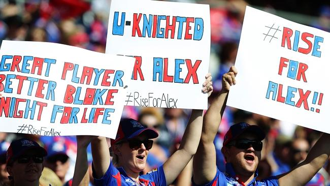 United ... Newcastle fans hold signs in respect for injured player Alex McKinnon during the Knight's round four game. Picture: Brett Costello