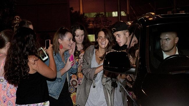 Justin Bieber poses for selfies with fans after arriving at Brisbane Airport, though his driver doesn't look so keen. Picture: Marc Grimwade/Getty Images