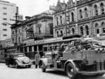 A fire truck passes a tram as it heads down King William St, circa 1951.