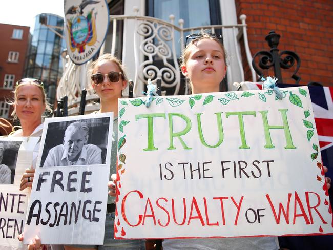 Pro-Assange demonstrators stand with placards at a vigil to mark the fifth anniversary of Julian Assange's arrival at the Embassy of Ecuador in London on Monday. Picture: Isabel Infantes/AFP