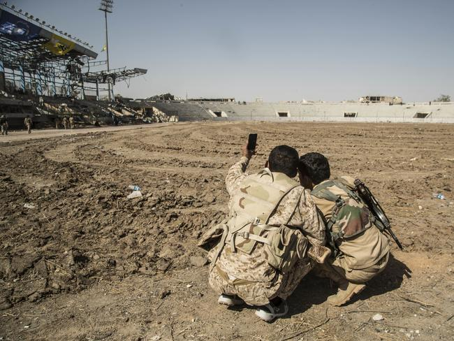 Members of the US-backed Syrian Democratic Forces (SDF) take a selfie the stadium. Picture: Asmaa Waguih