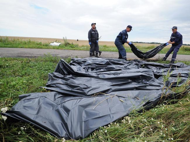 Ukrainian rescue workers collect bodies of victims at the site of the MH17 crash