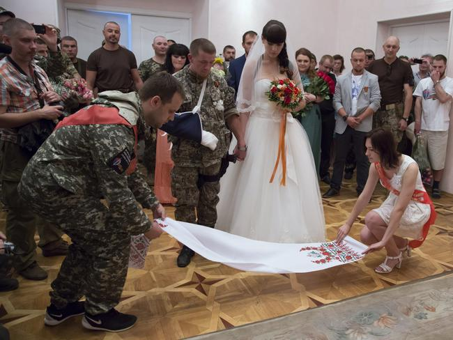 New sanctions applied ... Pavel Gubarev, left, leader of the self-proclaimed Donetsk People's Republic, attends the wedding ceremony of platoon commander Arsen Pavlov, also known as Motorola, and Elena Kolenkina.