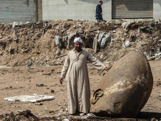 An Egyptian worker stands next to the head of the statue at the site of a new discovery. Picture: Khaled Desouki