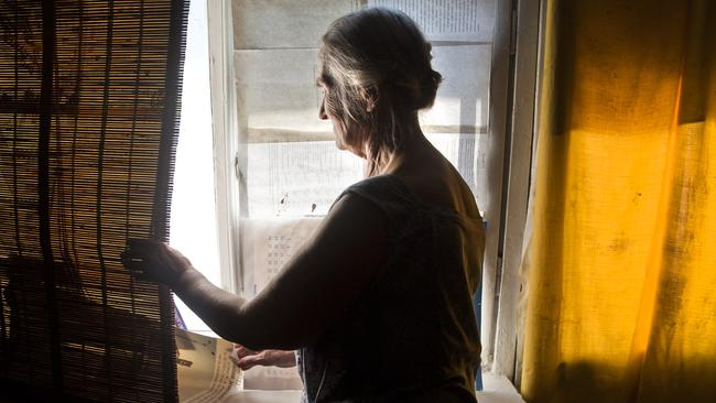 Valentina Kozlova's inspects the windows of her home unit shattered in a mortar attack in Donetsk. Picture: Ella Pellegrini