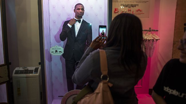 A woman takes pictures in front of a box where a man in a suit stands in the window of a store of an online dating site in Paris. Picture: AFP/Fred Dufour