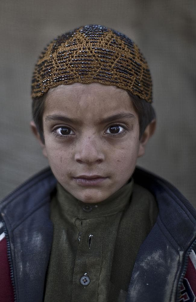 Afghan refugee boy, Allam Ahmad, 6, poses for a picture, while playing with other children in a slum on the outskirts of Islamabad, Pakistan.