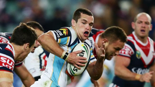 Gold Coast's Daniel Mortimer makes a break surrounded by Roosters.