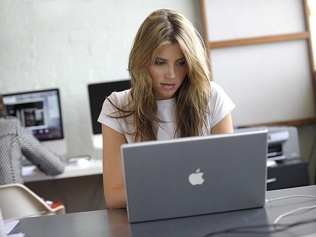 A woman works on an Apple MacBook at an office.