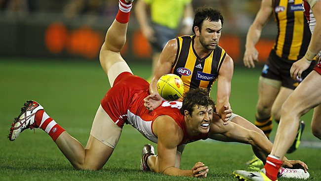 Hawk Jordan Lewis up-ends Swans forward Kurt Tippett during the hotly contested qualifying final. Picture: Wayne Ludbey