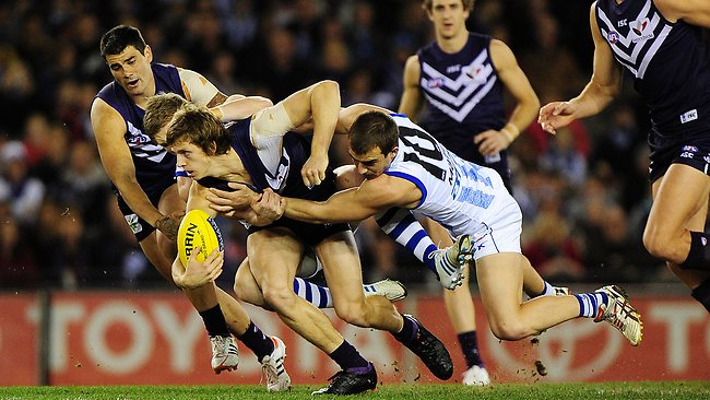 Jack Ziebell and Ben Cunnington tackle Nathan Fyfe in their clash at Etihad Stadium. Picture: George Salpigtidis