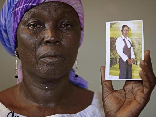 Unbearable anguish ... Martha Mark, the mother of schoolgirl Monica Mark, kidnapped by Boko Haram terrorists, cries as she displays her photo in the family house in Chibok, Nigeria.