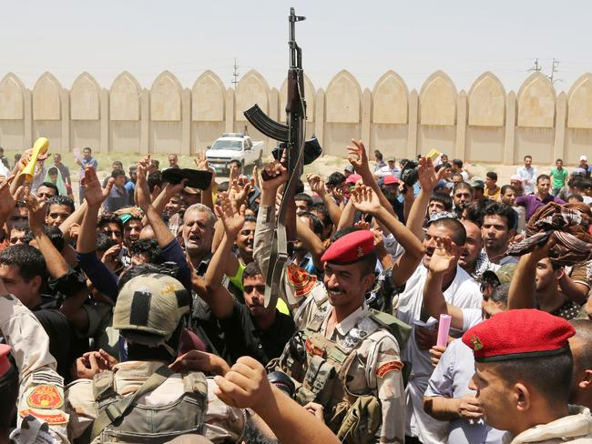 Growing support ... Iraqi soldiers and volunteers chant slogans against ISIS inside the main army recruiting centre in Baghdad. Iran has reportedly sent troops to assist in the defence of the capital.