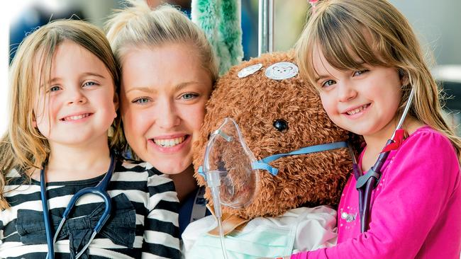 Sisters Amaia, 3 (left) and Natasha Aparo, 5, with trainee doctor and former Royal Children's Hospital patient Megan Dynan at this year's Good Friday Appeal.