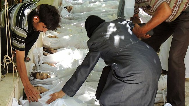 A handout image released by the Syrian opposition's Shaam News Network shows a woman mourning over a body wrapped in shrouds laid out in a line on the ground with other victims which Syrian rebels claim were killed in a toxic gas attack by pro-government forces.