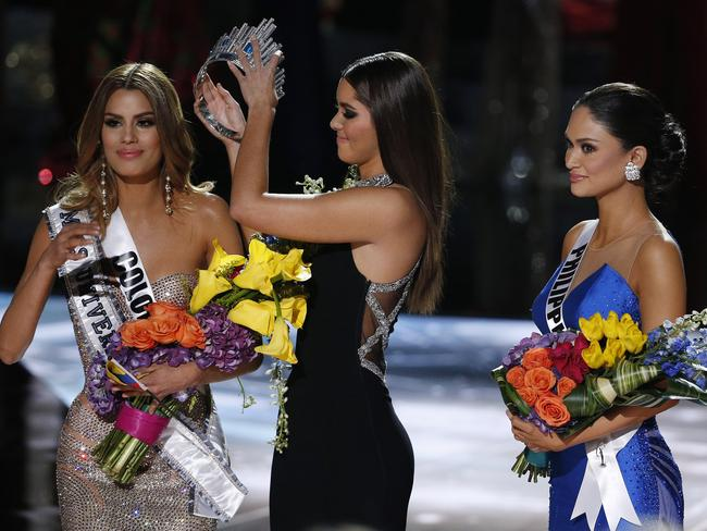 Former Miss Universe Paulina Vega, center, removes the crown from Miss Colombia Ariadna Gutierrez, left, before giving it to Miss Philippines Pia Alonzo Wurtzbach. AP Photo/John Locher.
