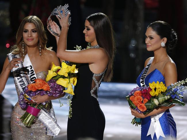 Former Miss Universe Paulina Vega ... removes the crown from Miss Colombia Ariadna Gutierrez before giving it to Miss Philippines Pia Alonzo Wurtzbach. Picture: AP