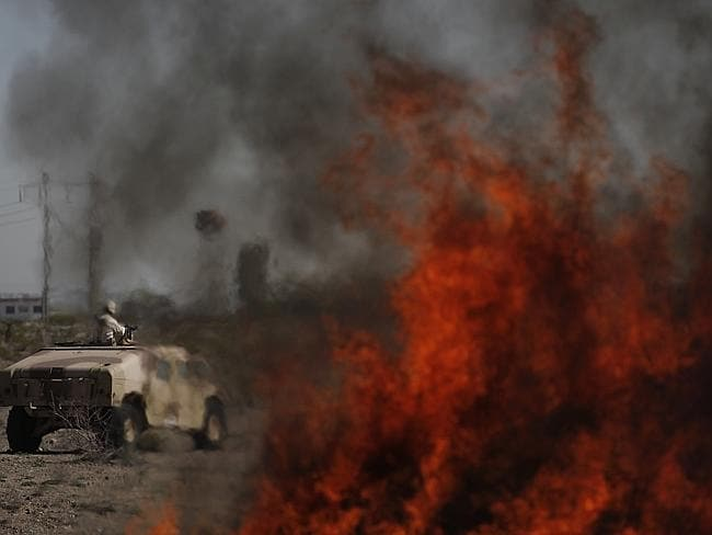 A soldier stands on a vehicle behind a burning pile of over two tons of seized marijuana and cocaine in Ciudad Juarez, Mexico.