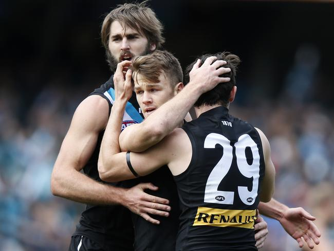 Justin Westhoff, Robbie Gray and Jasper Pittard hug after a Gray goal. Photo: Sarah Reed.