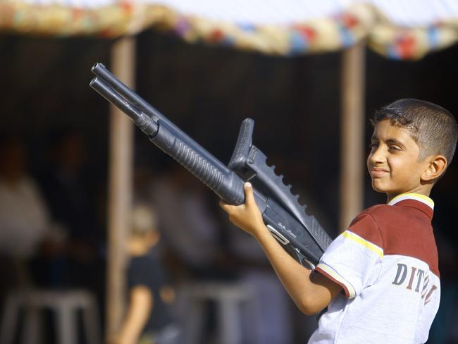 Revenge attacks ... an Iraqi boy holds a weapon as he takes part in a gathering by Shiite tribesman to show their willingness to join Iraqi security forces in the fight against Jihadist militants.