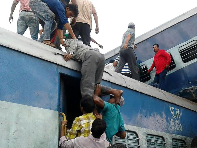 Local residents look for survivors on the wreckage of train carriages after an express train derailed near the town of Khatauli in the Indian state of Uttar Pradesh on August 19, 2017. Picture: AFP.