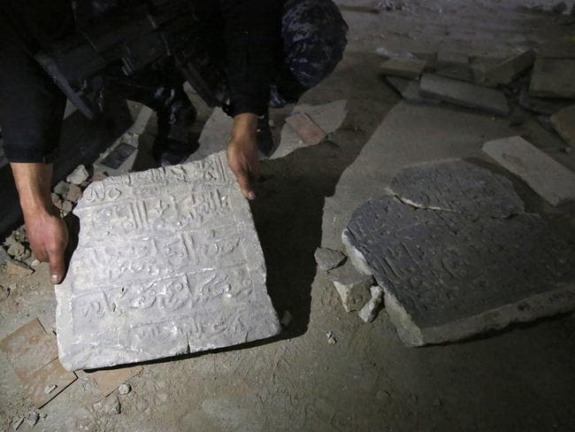 A member of the Iraqi forces holds damaged artefacts inside the destroyed museum. Picture: Ahmad Al-Rubaye
