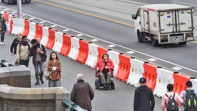White and orange plastic bollards have been placed along the Princes Bridge to prevent pedestrians from vehicles. Picture: Tony Gough