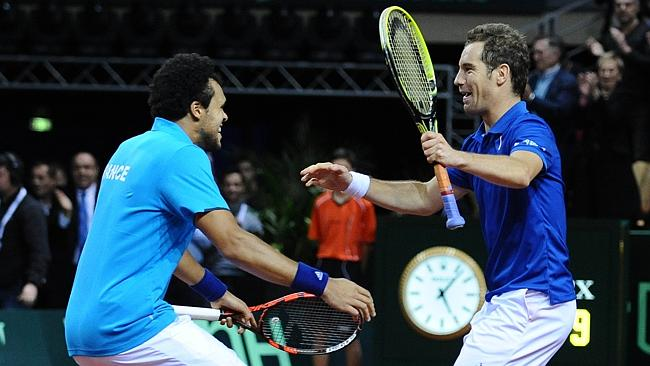 France's Jo-Wilfried Tsonga celebrates with teammate Richard Gasquet after winning the doubles against Australia's Lleyton He...