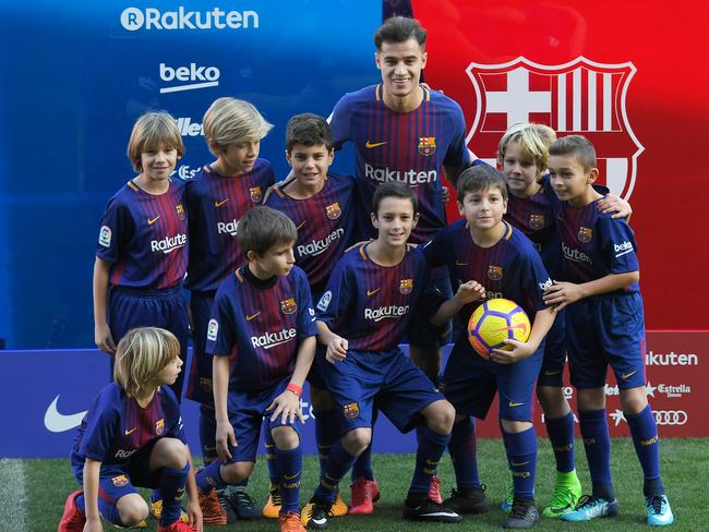 Barcelona's new Brazilian midfielder Philippe Coutinho poses with a group of children