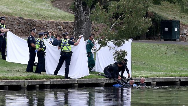 Divers in the water as police hold up a sheet to shield the view from onlookers as they retrieve the body of a man from the river. Photo: Mike Burton, The Advertiser