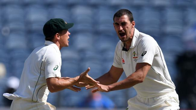 Australia's Mitchell Starc (R) celebrates with teammate Steve O'Keefe after the dismissal of India's captain Virat Kohli during the second day of the first cricket Test match between India and Australia at The Maharashtra Cricket Association Stadium in Pune on February 24, 2017. ----IMAGE RESTRICTED TO EDITORIAL USE - STRICTLY NO COMMERCIAL USE----- / GETTYOUT / AFP PHOTO / INDRANIL MUKHERJEE / ----IMAGE RESTRICTED TO EDITORIAL USE - STRICTLY NO COMMERCIAL USE----- / GETTYOUT