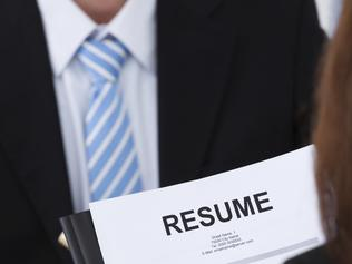 CAREERS: Cropped image of female candidate holding resume at desk during interview. Source: iStock