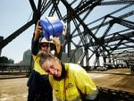 Jerry Gunnis cools down Lisa Jay with some iced water as they work on resurfacing Brisbane's Story Bridge. Pic: Mark Calleja