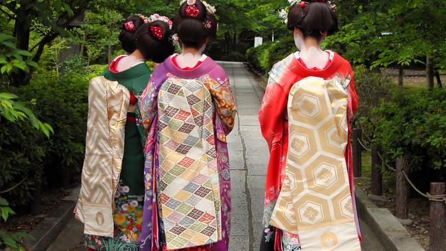 A group of geishas visiting a garden in Japan..