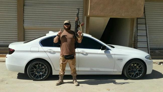 Australian Khaled Sharrouf posing with an AK-47 in front of a sports car from an undisclosed location within Iraq. Picture: Twitter