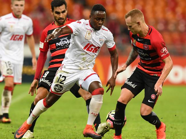 Adelaide United's Mark Ochieng looks to get between Wanderers players Dimas Delgado (left) and Jack Clisby on Saturday night.