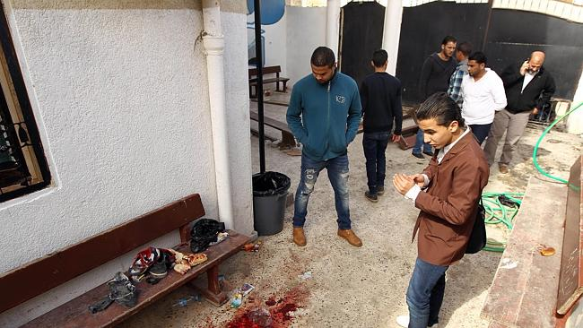 Attack on children ... Libyan youths at a primary school in Benghazi where a bomb injured 12 children.