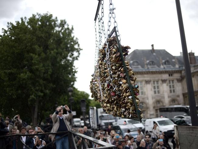 End of an era ... people take photographs as workers remove panels bearing love padlocks attached on the railings of the Pont des Arts bridge. Picture: AFP/Stephane De Sakutin