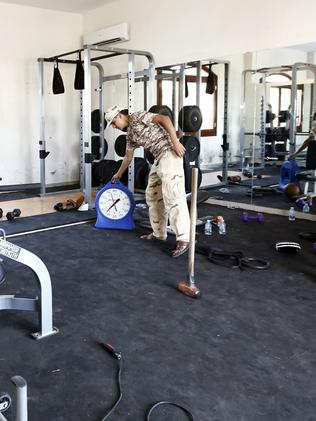 'No damage' ... a member of the Fajr Libya (Libya Dawn) Islamist militia stands at the gym of a villa at the US diplomatic compound. Pictuer: Mahmud Turkia