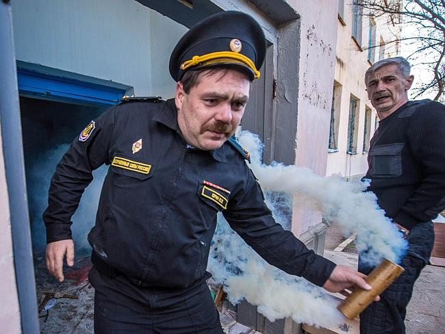 Tensions ... A man prepares to throw a smoke bomb as pro-Russian protesters storm an Ukra