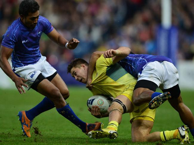 Greg Jeloudev of Australia (C) is tackled by Samoa players during the rugby sevens bronze medal match.