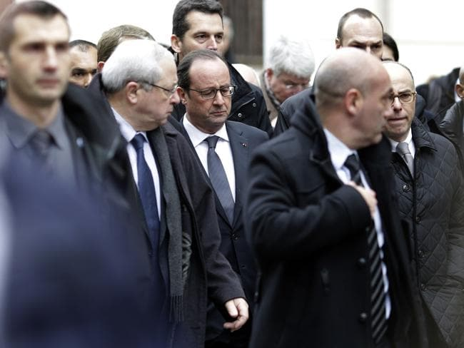 French President Francois Hollande (C) arrives at the headquarters of the French satirical newspaper Charlie Hebdo in Paris. Picture: AFP