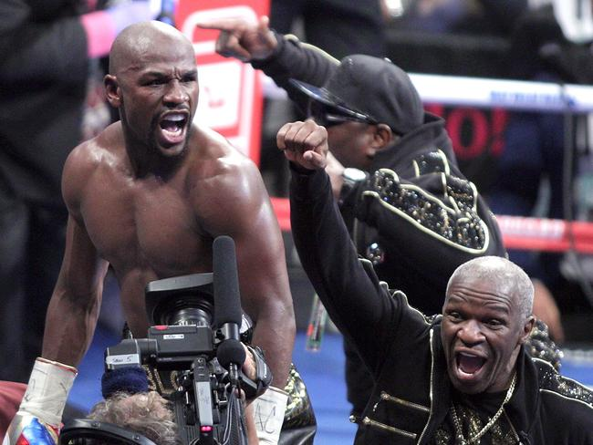 Floyd Mayweather celebrates his 10th round TKO victory over mixed martial arts star Conor McGregor along his dad, Floyd Mayweather Snr, in Las Vegas, Nevada. Picture: John Gurzinski/AFP