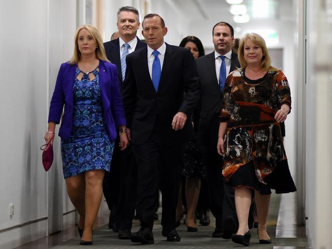 Tony Abbott arrives surrounded by fellow MPs for a leadership ballot of the Liberal Party at Parliament House. Picture: AAP/Lukas Coch