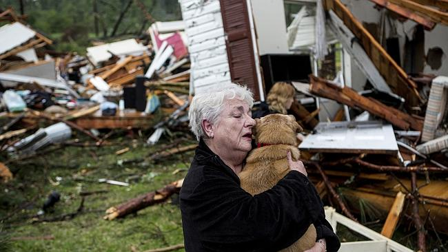 Heartbreak ... Constance Lambert embraces her dog after finding it alive when returning to her destroyed home in Tupelo.