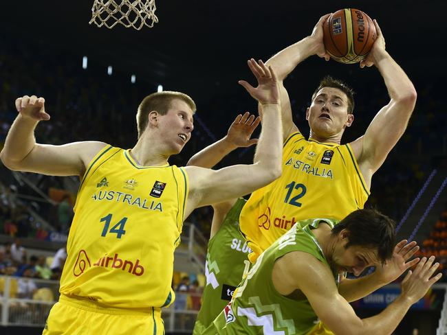 Australia's Aron Baynes grabs the ball next to teammate Brock Motum and Slovenia's Domen Lorbek.