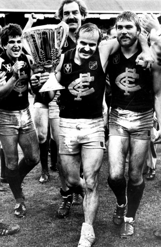 Carlton playing-coach Alex Jesaulenko walks off the MCG with a bandaged injured foot and the 1979 premiership cup.