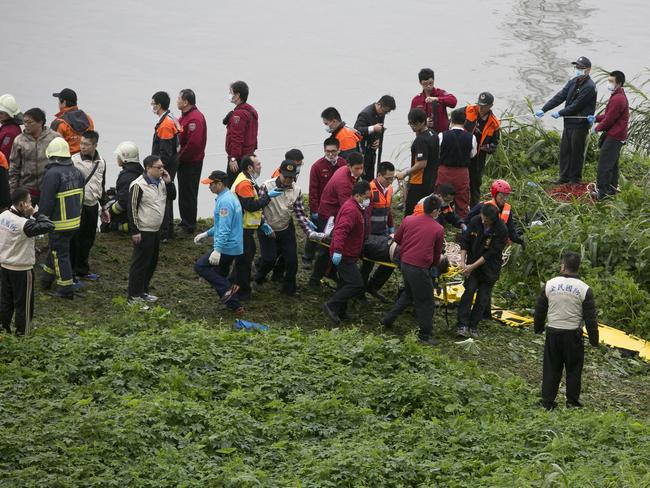 Moving the injured ... a rescue crew carries a passenger from a TransAsia Airways ATR 72-600 turboprop aeroplane. Picture: Ashley Pon/Getty Images